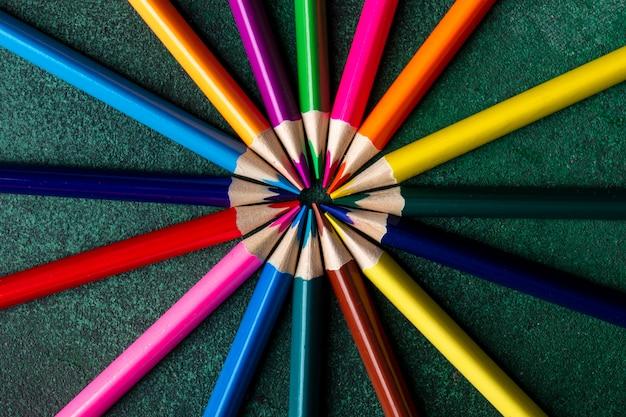 Vista superior de lápis de cor, dispostas no escuro