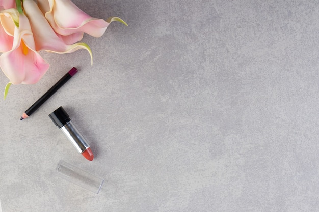 Vista superior de lápis e batom na superfície cinza