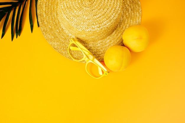 Vista superior de laranjas com óculos de sol, chapéu e folhas de palmeira isoladas em uma superfície amarela