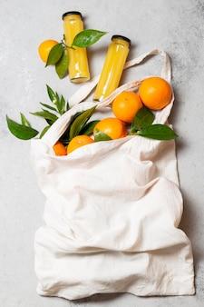 Vista superior de laranjas em sacola com garrafas de suco