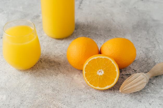 Vista superior de laranjas frescas e suco de laranja em vidro, espremedor de frutas de madeira