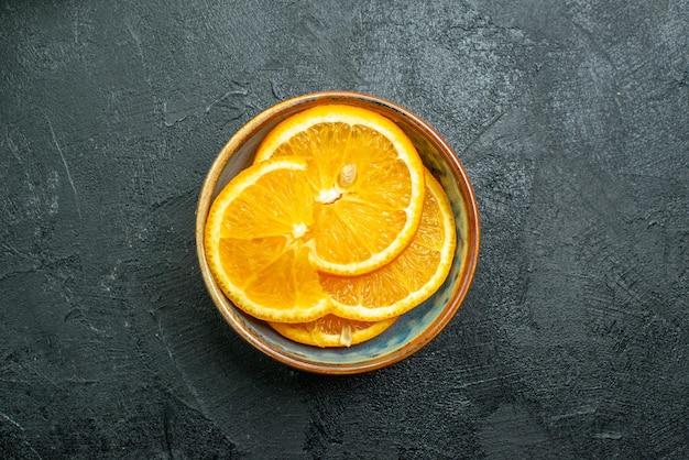 Vista superior de laranjas frescas fatiadas dentro do prato em superfície escura com suco de frutas tropicais cítricas