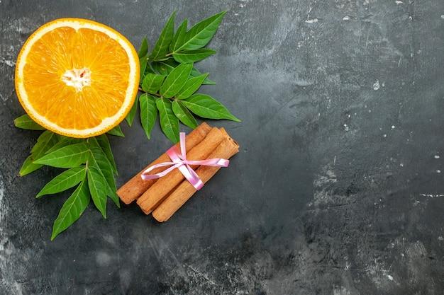Vista superior de laranjas frescas naturais de fonte de vitamina com folhas de lima e canela em fundo cinza