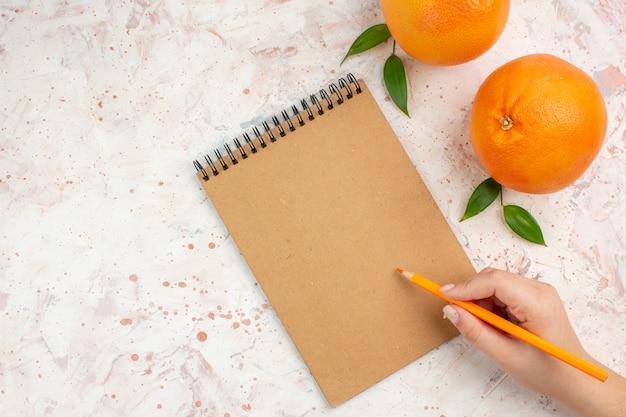Vista superior de laranjas frescas, um lápis de bloco de notas em uma mão feminina em um lugar livre de superfície brilhante