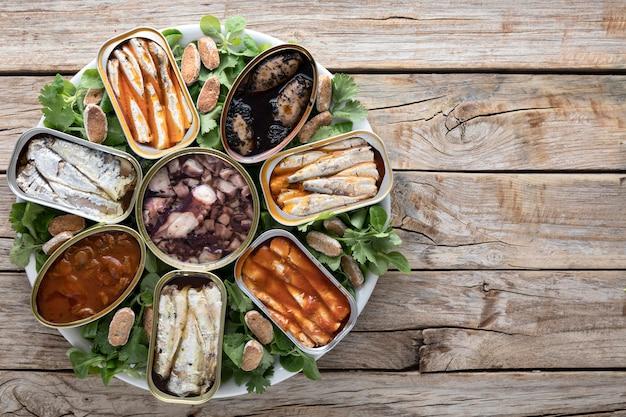 Vista superior de latas de frutos do mar no prato com espaço de cópia