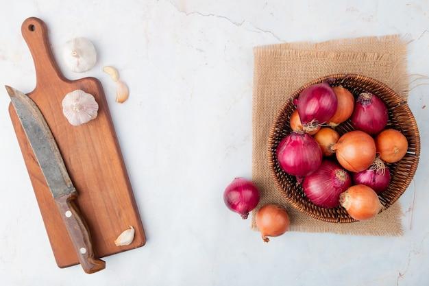 Vista superior de legumes como alho e cesto de cebola com tábua e faca em fundo branco