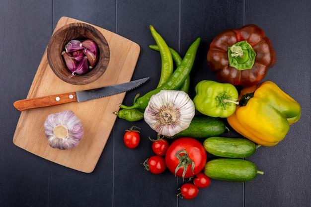 Vista superior de legumes como alho e cravo com faca na tábua e tomate pepino pimenta na superfície preta