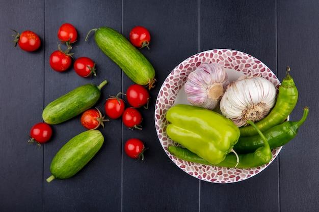 Vista superior de legumes como alho pimenta no prato com tomates e pepinos na superfície preta