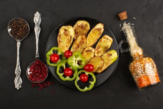 Vista superior de legumes, como berinjela cozida, pimentão verde fresco e tomate cereja vermelho dentro de chapa preta
