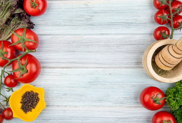 Vista superior de legumes como coentro de tomate com triturador de alho pimenta nos lados esquerdo e direito e superfície de madeira com espaço de cópia