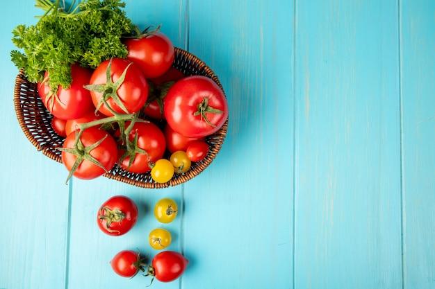 Vista superior de legumes como coentro e tomate na cesta no lado esquerdo e superfície azul com espaço de cópia