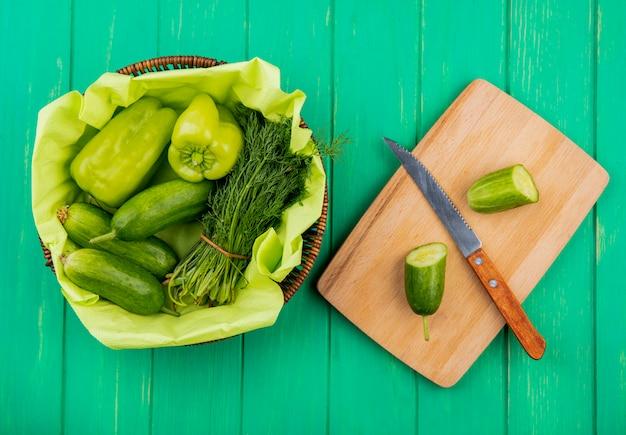 Vista superior de legumes como endro de pepino pimenta na cesta com pepino cortado e faca na tábua na superfície verde