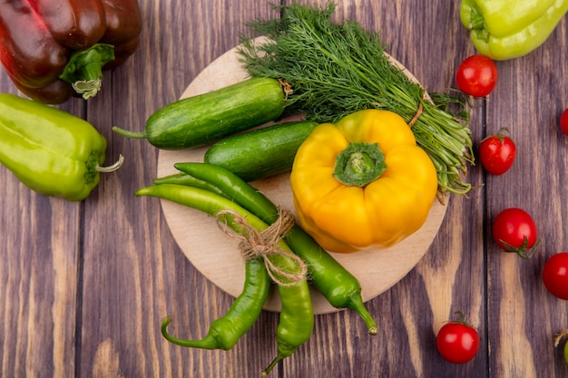 Vista superior de legumes como endro de pepino pimenta na tábua com tomates na superfície de madeira