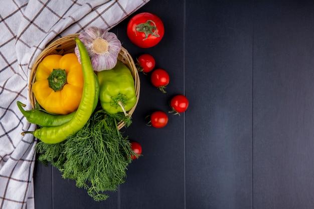 Vista superior de legumes como endro de pimenta alho na cesta com tomates e pano xadrez na superfície preta