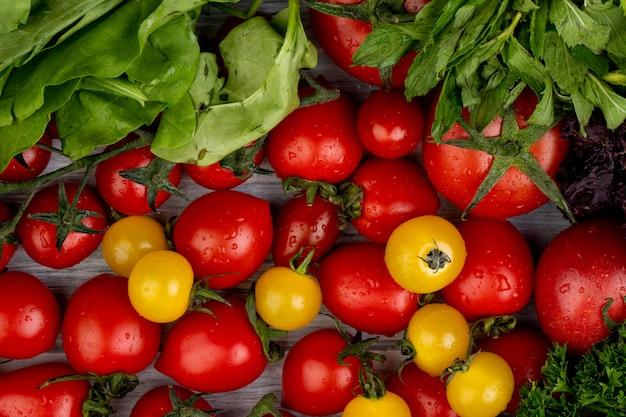 Vista superior de legumes como folhas de hortelã espinafre verde coentro e tomate na madeira