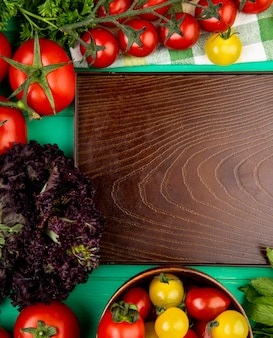 Vista superior de legumes como folhas de hortelã verde tomate manjericão em torno da bandeja vazia na superfície verde