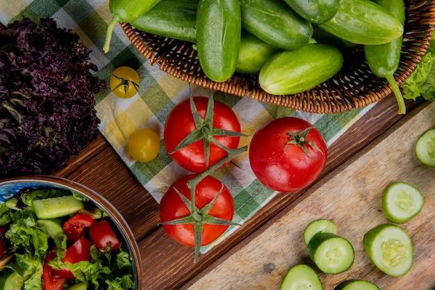Vista superior de legumes como manjericão de pepino de tomate com salada de legumes na superfície de madeira