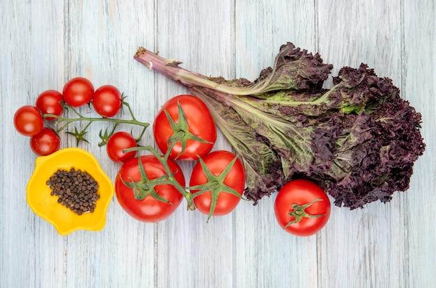 Vista superior de legumes como manjericão de tomate com uma tigela de sementes de pimenta preta na superfície de madeira