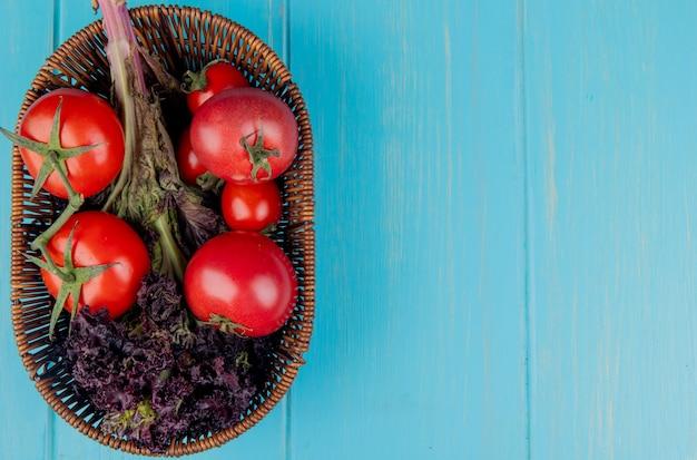 Vista superior de legumes como manjericão e tomate na cesta no lado esquerdo e superfície azul com espaço de cópia