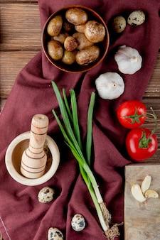 Vista superior de legumes como ovo de alho cebolinha tomate com batata cozida e triturador de alho no pano de borgonha e fundo de madeira