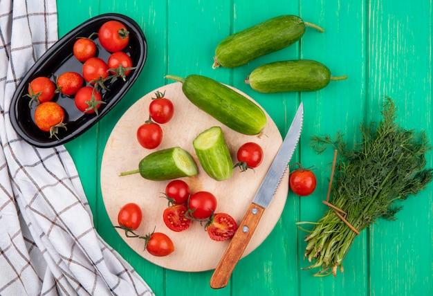 Vista superior de legumes como pepino e tomate com faca na tábua e monte de endro na superfície verde