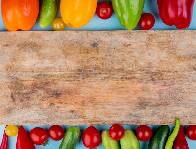Vista superior de legumes como pepino tomate pimenta com placa de corte na superfície azul