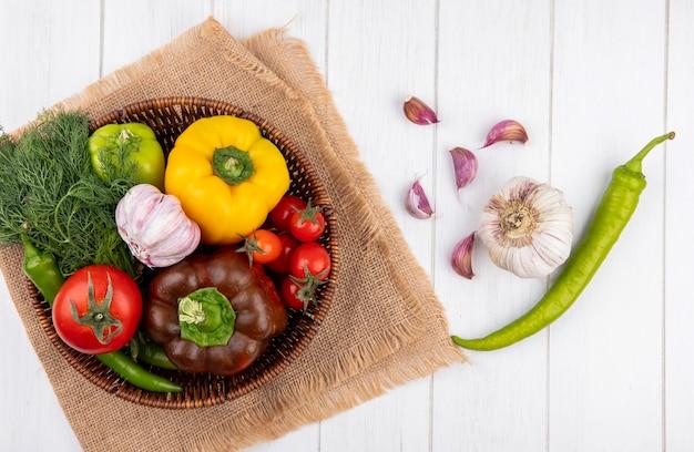 Vista superior de legumes como pimenta alho endro tomate na cesta de saco com dentes de alho na superfície de madeira