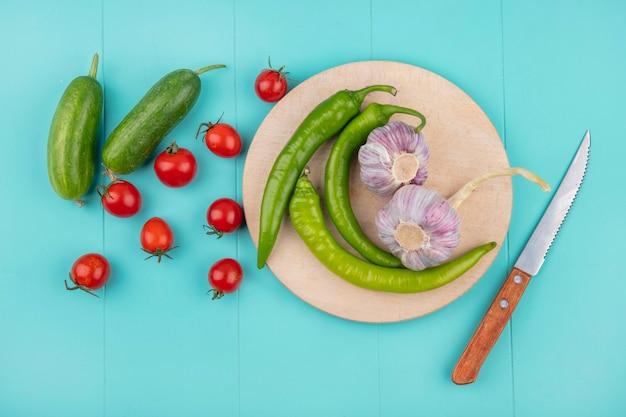 Vista superior de legumes como pimenta e alho na tábua com pepino tomate e faca na superfície azul