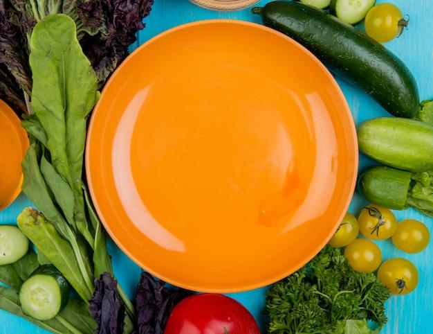 Vista superior de legumes como tomate de pepino manjericão espinafre com prato na superfície azul