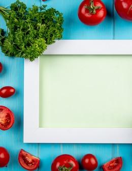 Vista superior de legumes como tomate e coentro em torno da placa na superfície azul com espaço de cópia
