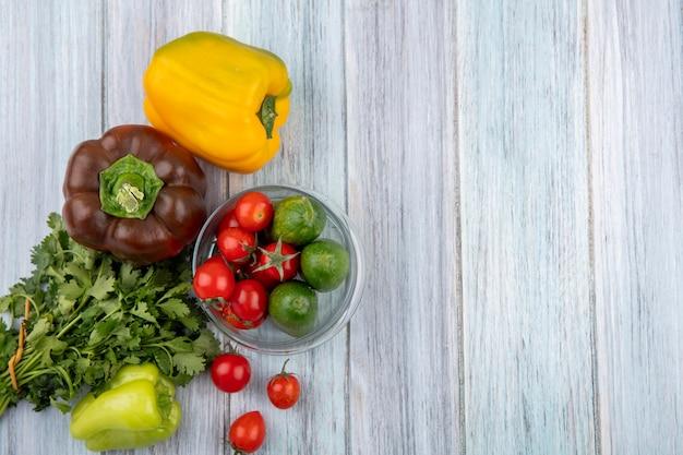 Vista superior de legumes como tomate e pepino em uma tigela com pimenta e monte de coentro na superfície de madeira