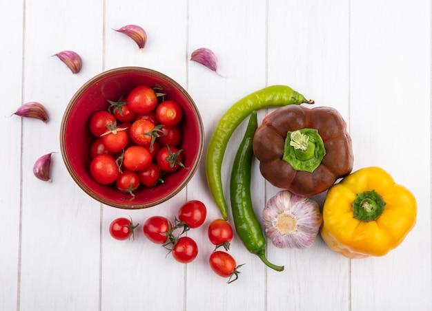Vista superior de legumes como tomate em tigela pimentas alho bulbo e cravo na superfície de madeira