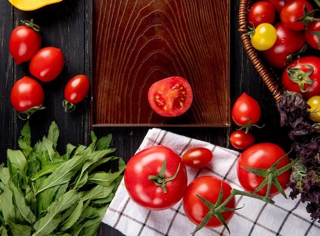 Vista superior de legumes como tomate manjericão na cesta e tomate cortado na bandeja com folhas de hortelã verde na madeira