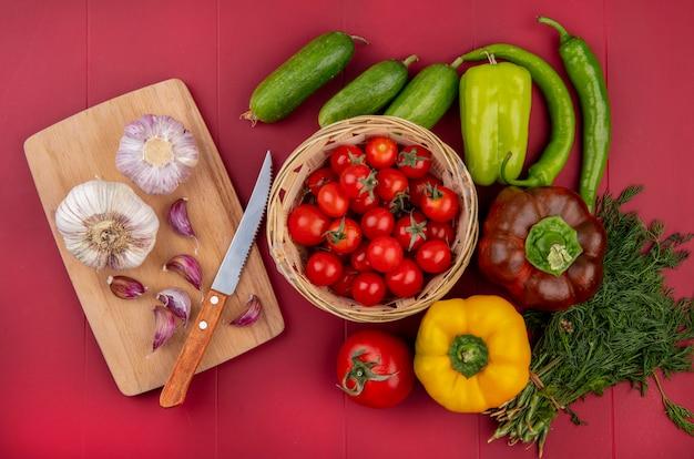 Vista superior de legumes como tomate na cesta pepinos pimentão endro e alho com faca na tábua na superfície vermelha