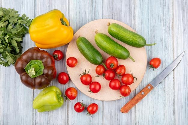 Vista superior de legumes como tomate pepino na tábua com coentro de pimenta e faca na superfície de madeira
