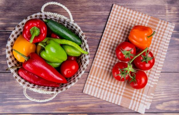 Vista superior de legumes como tomate pepino pimenta na cesta com tomates e pimenta no pano xadrez e madeira