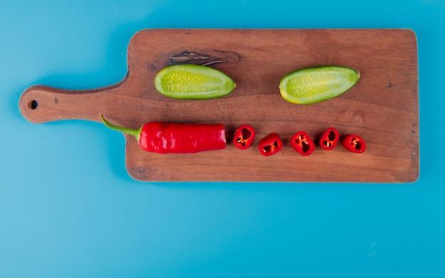 Vista superior de legumes cortados e fatiados como pimenta e pepino na tábua e superfície azul com espaço de cópia