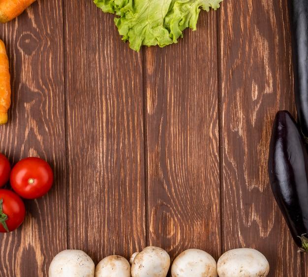 Vista superior de legumes dispostos como um quadro berinjela cenoura tomate e cogumelos no fundo rústico de madeira com espaço de cópia