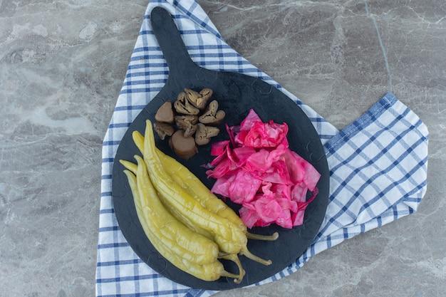 Vista superior de legumes em conserva na placa de corte preta.