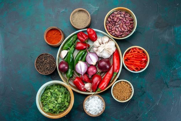 Vista superior de legumes frescos cebolas alho pimentas com verduras e feijão no escuro, vegetal ingrediente de refeição alimentar