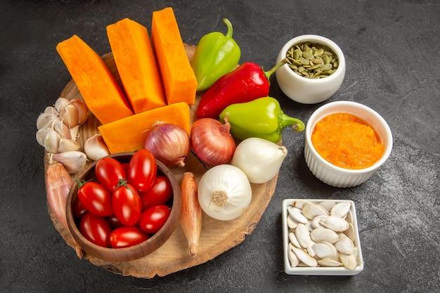 Vista superior de legumes frescos com abóbora fatiada em fundo cinza cor de salada madura fresca