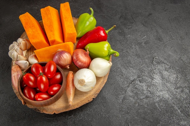 Vista superior de legumes frescos com abóbora fatiada em fundo cinza escuro cor de salada madura fresca
