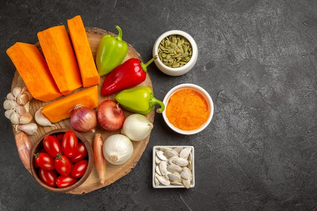 Vista superior de legumes frescos com abóbora fatiada na salada madura de cor fresca de fundo cinza
