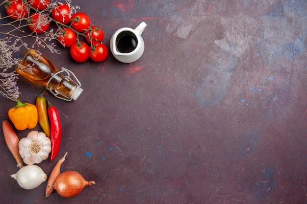 Vista superior de legumes frescos com azeite de oliva na mesa escura