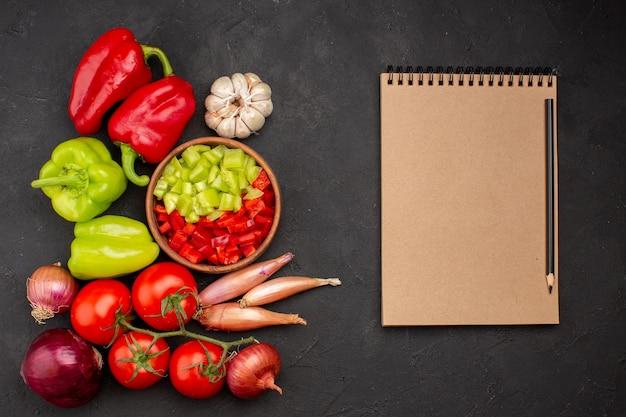 Vista superior de legumes frescos com bloco de notas em fundo cinza