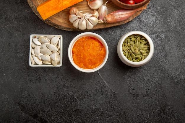 Vista superior de legumes frescos com fatias de abóbora e alho na cor de semente de fundo cinza salada madura fresca