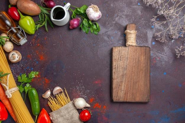 Vista superior de legumes frescos com massa crua e mesa na superfície escura, salada de refeição de comida madura