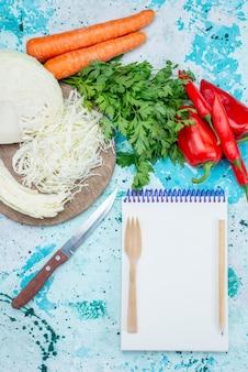 Vista superior de legumes frescos, fatias de repolho, cenouras e pimentões com o bloco de notas na mesa azul brilhante