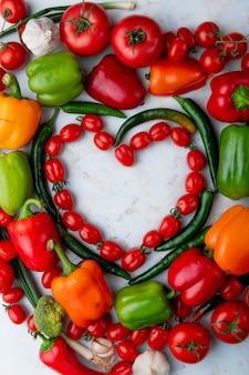 Vista superior de legumes frescos maduros, dispostos em forma de coração tomate cereja pimentão verde pimentão alho e cebola no fundo de mármore