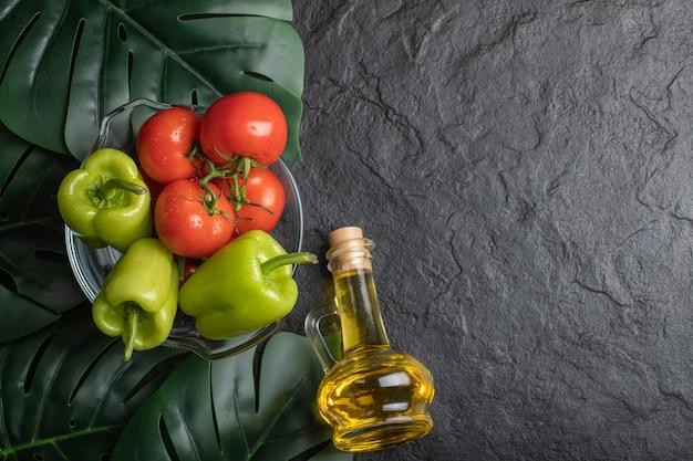 Vista superior de legumes frescos, tomate e pimenta em uma tigela de vidro e uma garrafa de óleo.